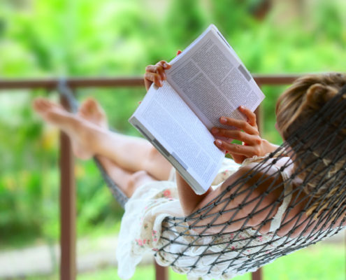 Woman-Relaxing-in-Hammock-with-Book